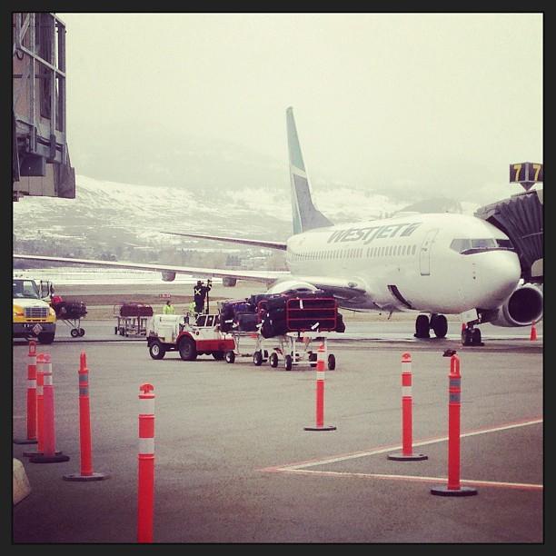 A WestJet flight from Toronto is parked outside the terminal in Kelowna.